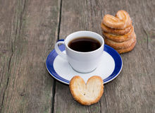 Coffee on a saucer, and a column from cookies, on a wooden table Stock Photos