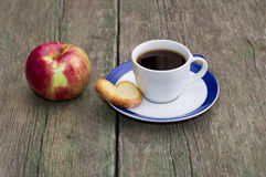 Coffee on a saucer, cookies and one apple, on a wooden table Royalty Free Stock Image