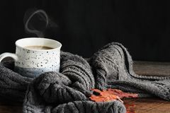 Coffee and Scarf. Hot steaming cup of coffee with cream wrapped in a cozy grey scarf with fallen leaves for autumn. Extreme shallow depth of field with selective royalty free stock images