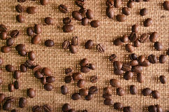 Coffee  scattered on brown burlap Royalty Free Stock Photos