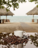 Coffee sea. Cup full of coffee beans on a glass table on the beach stock image