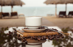 Coffee sea horizontal. Cup of coffee on a book on the beach stock photos