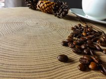 Coffee seeds and coffee cup on wooden table stock image