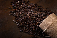 Coffee seeds with some jute bags filled with coffee beans. Jute bags. Low light Royalty Free Stock Images