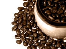 Coffee Series 1. Half of a mug filled with coffee beans, surrounded by more coffee beans. Coffee beans on the surface in focus Stock Photo