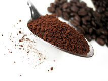 Coffee Series 7. Coffee beans and ground coffee : Transition. Focus on spoonful of ground coffe Royalty Free Stock Images