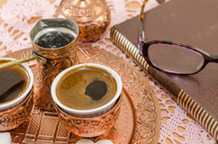 Coffee served in copper pottery and a book Royalty Free Stock Photography