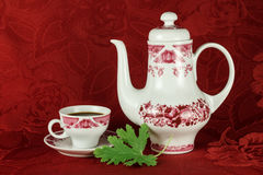 Coffee service. Elegant white and red coffee set against the background of the red tablecloths Stock Image