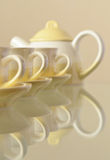 Coffee set. A set of cups and coffee pot on a glass table Stock Image