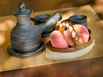 Coffee set and ceramic vase with peaches. Coffee set and ceramic vase with peaches on a table Royalty Free Stock Photo