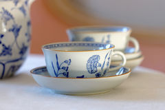 Coffee set made of white and blue porcelain. On a table with linen cloth and a pink wall behind Stock Image