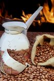 Coffee set and scattered beans,  open fireplace in background XX Royalty Free Stock Photography