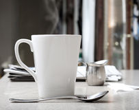 Coffee Shop. Mug of hot coffee or tea with stainless creamer and morning newspaper on counter. Intentionally desaturated for effect Stock Image