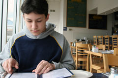 At a coffee shop. Boy sitting in a coffee shop Royalty Free Stock Photos