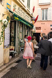 Coffee shop in Antibes. Le Cafe Jardin at the commercial center of Antibes on a pedestrian street. A woman with red short hair and a dress with square pattern Stock Photography