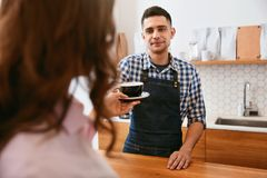 Coffee Shop. Barista Giving Cup Of Coffee To Customer Royalty Free Stock Image