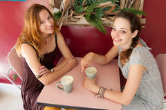 Coffee Shop - Casual conversation. Two women enjoy a conversation over coffee at a small shop Royalty Free Stock Images