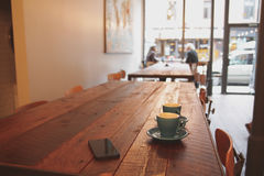 Coffee shop with cups on table Stock Photography