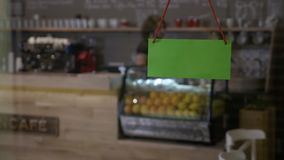 Coffee shop owner serving clients and then taking his apron off and flipping over green screen closing sign. Coffee shop owner serving last clients and then stock footage