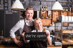 Coffee shop owners showing open sign. Coffee shop owners holding and  showing open sign Royalty Free Stock Image