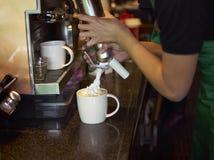 Coffee shop staff making coffee. Closeup of a coffee shop waiter making coffee Royalty Free Stock Photos