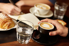 Coffee shop table with hands, espresso and someone writing. Cropped closeup of a hand holding an espresso with a heart pattern in it, with other items on the stock photo
