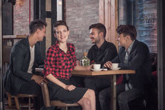 Coffee shop table, small group of people talking, sitting in bar. Young adults, coffee shop table, small group of people talking, sitting in bar stool, happy Royalty Free Stock Photo