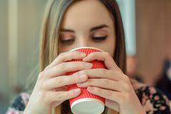 Coffee shop tasty hot morning beverage takeaway to go paper red cup tea enjoy face happiness hands holding concept. Close up view. Photo portrait of beautiful Royalty Free Stock Photography