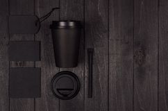 Coffee shop template for branding identity - black paper cup, white cap, blank label, card, cap, sugar on black wood board. Coffee shop template for branding stock images
