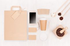 Coffee shop template for branding identity - brown paper cup with blank bag, phone, label, card, mortar with coffee beans on white. Wood board, top view royalty free stock images