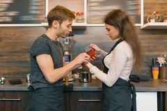 Coffee shop workers young smiling man and woman making coffee with machine, professional baristas team cafe business stock photo
