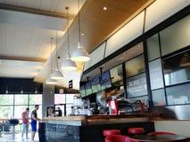 Coffee shopinre och två manliga kunder i bakgrund Arkivbild