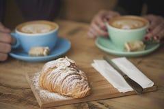 Coffee shopvänner som har ett mellanmål Arkivfoto