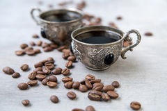 Coffee in silver vintage cups on wooden background. Close-up of coffee in silver vintage cups on wooden background, Arabic style, selective focus Royalty Free Stock Photo