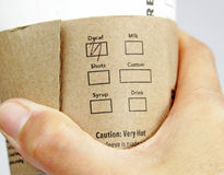 Coffee Sleeve. Hand holding a commercial cup with earth friendly safety sleeve marked with the decaf selection stock photography