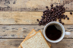Coffee,slice of bread and coffee beans on wooden table Royalty Free Stock Photography