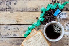 Coffee,slice of bread,measuring tape and coffee beans on wooden Royalty Free Stock Photography