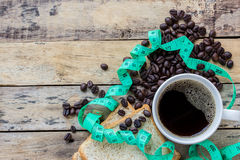 Coffee,slice of bread,measuring tape and coffee beans on wooden Stock Photography