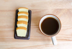 Coffee and slice of butter cake on table Stock Photos