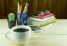 Coffee,smart phone,glasses,and stack of book on wooden Stock Image