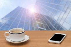 Coffee and smart phone on wooden table with building blur stock photos