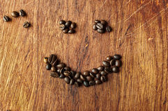 Coffee smile. Coffee beans on the background of wood texture Stock Images