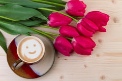 Coffee smiley face with red tulips on wood. Top view Stock Images