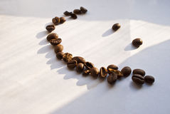 Coffee smiling. Smile made ​​of coffee beans on a white sheet Royalty Free Stock Image