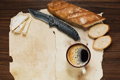 Coffee and some appetizers on the old paper sheets. A cup coffee, baguette bread and camembert cheese on the background of old paper sheets royalty free stock image