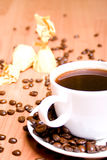 Coffee, some sweets and beans. Cup of coffee, some sweets and beans on wooden table Royalty Free Stock Images