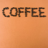 Coffee spelled out with roasted coffee beans, on orange backgrou Royalty Free Stock Photography