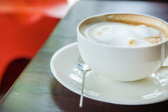Coffee with spice and artistic foam in a white cup Stock Image