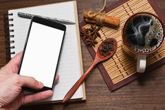 Coffee with spices, diary and a cell phone in hand. Top view of coffee cup, different spices, notebook with a pen and a smartphone or small tablet in male hand stock photo