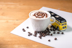 Coffee with spider pattern  in a white cup and car toy Royalty Free Stock Images